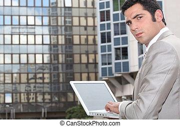 Un hombre usando su portátil fuera de una oficina