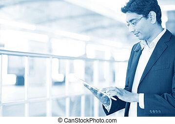 Un hombre usando tablet pc en la estación de tren