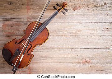 Un instrumento de violín en el suelo de madera con espacio de copia