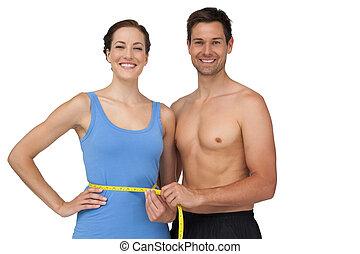 Un joven adecuado midiendo la cintura de una mujer