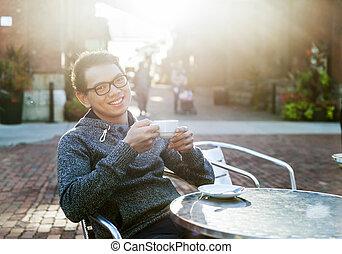 Un joven asiático en un café al aire libre