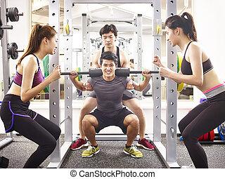 Un joven asiático levantando peso en el gimnasio