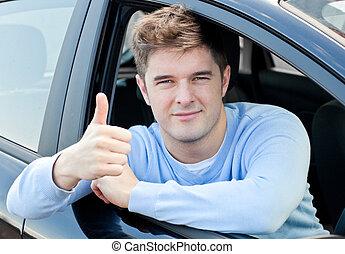 Un joven atractivo sentado en su auto con el pulgar hacia arriba