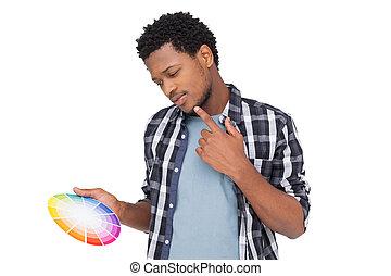 Un joven buscando muestras de pintura