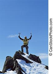 Un joven celebrando llegar a la cima de una montaña