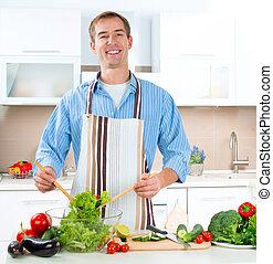 Un joven cocinando. Comida saludable, ensalada vegetal