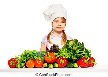 Un joven cocinero de uniforme con verduras frescas