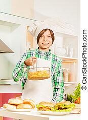 Un joven cocinero que prepara comida americana tradicional