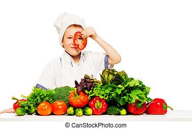 Un joven cocinero que se divierte con verduras frescas