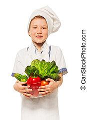 Un joven cocinero sonriente con un tazón de vegetales frescos