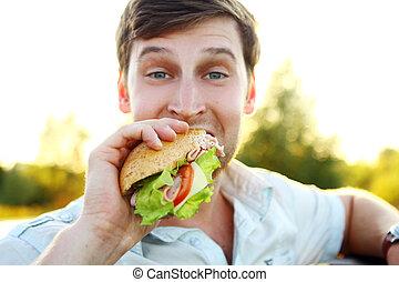 Un joven comiendo sándwich