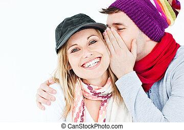 Un joven con gorra susurrando algo a su amiga