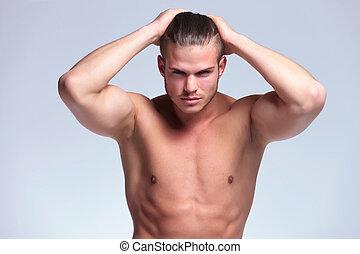 Un joven con las manos en el pelo