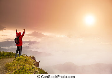 Un joven con mochila en la cima de la montaña mirando el amanecer