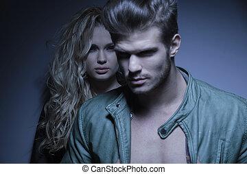 Un joven de la moda parado frente a su novia