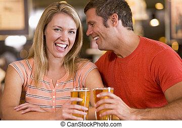 Un joven en el bar susurrando al oído de sus novias