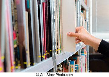 Un joven estudiante recogiendo un libro de la estantería de la biblioteca. Preparando exámenes, joven buscando o eligiendo un libro en la biblioteca pública de la universidad