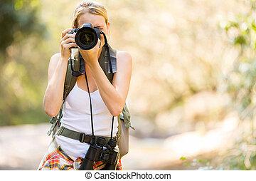 Un joven excursionista tomando fotos en la montaña