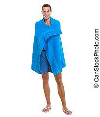 Un joven feliz envuelto en una toalla azul de playa
