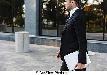 Un joven hombre de negocios caminando al aire libre con ordenador portátil.