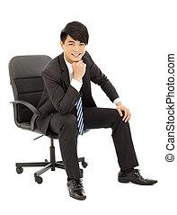 Un joven hombre de negocios inteligente sentado en una silla