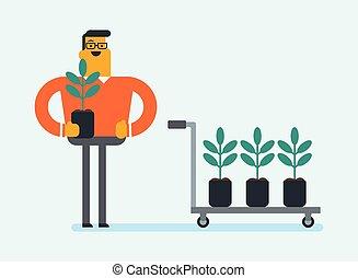 Un joven jardinero blanco caucásico plantando árboles.