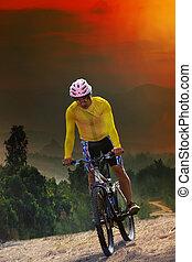Un joven montando en bicicleta de montaña cruzando la pista de la montaña con una oscura escena del cielo usada para el deporte de la puerta y el estilo de vida de actividades exteme