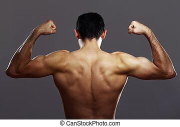 Un joven musculoso de fondo gris