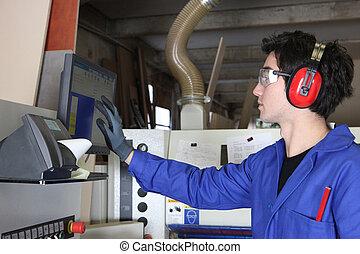 Un joven operando maquinaria de fábrica