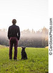 Un joven parado en medio de Green Meadow con su perro negro sentado mirándolo