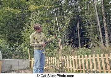 Un joven podando un árbol en el jardín
