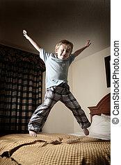Un joven saltando sobre la cama