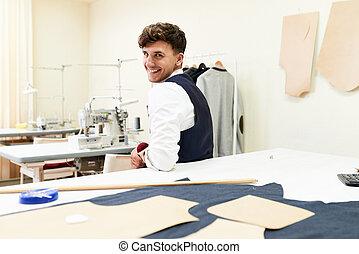 Un joven sastre alegre en el taller