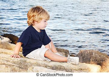 Un joven sentado al borde de un lago