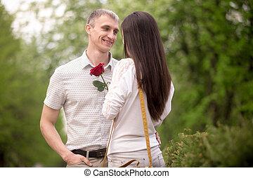 Un joven sonriente dando flores