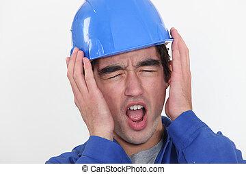 Un joven trabajador manual escuchando un ruido insoportable.