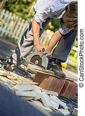 Un joven trabajando en su patio trasero usando sierra circular