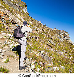 Un joven turista tomando fotos al aire libre en la montaña