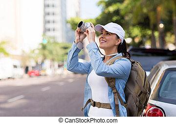 Un joven turista tomando fotos en la calle urbana