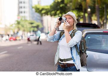 Un joven turista tomando fotos en la ciudad