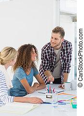 Un joven y feliz equipo de diseño teniendo una reunión juntos