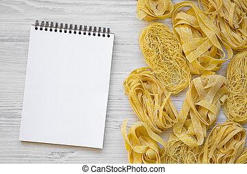 Un juego de pasta sin cocinar con cuaderno en un fondo blanco de madera, plano. Arriba, desde arriba.