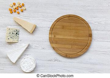 Un juego de queso con tablas de bambú redondas en un fondo blanco de madera. Copia espacio. Desde arriba, plano.