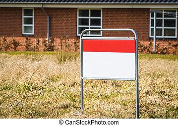 Un letrero de bienes raíces en el césped frente a una casa