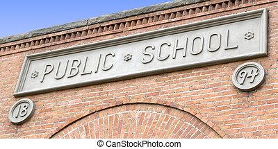Un letrero de la escuela pública en el edificio de ladrillos