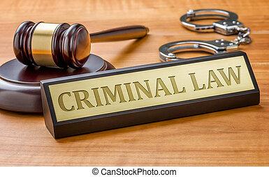 Un martillo y un nombre con la ley criminal grabado