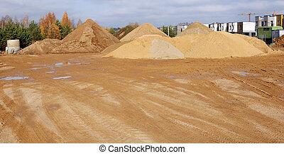 Un montón de arena de construcción con trazas de ruedas tractores en la construcción de la ciudad