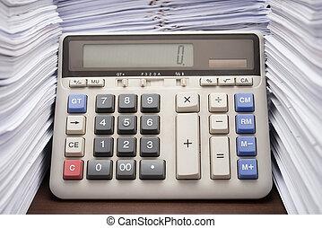 Un montón de documentos en escritorios con una calculadora en la oficina