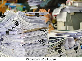 Un montón de documentos en la mesa de arriba esperando ser manejados.