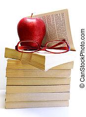 Un montón de libros con manzanas y gafas aisladas